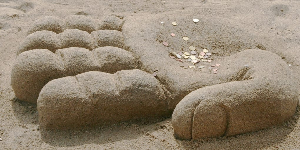 Sand hand with coins